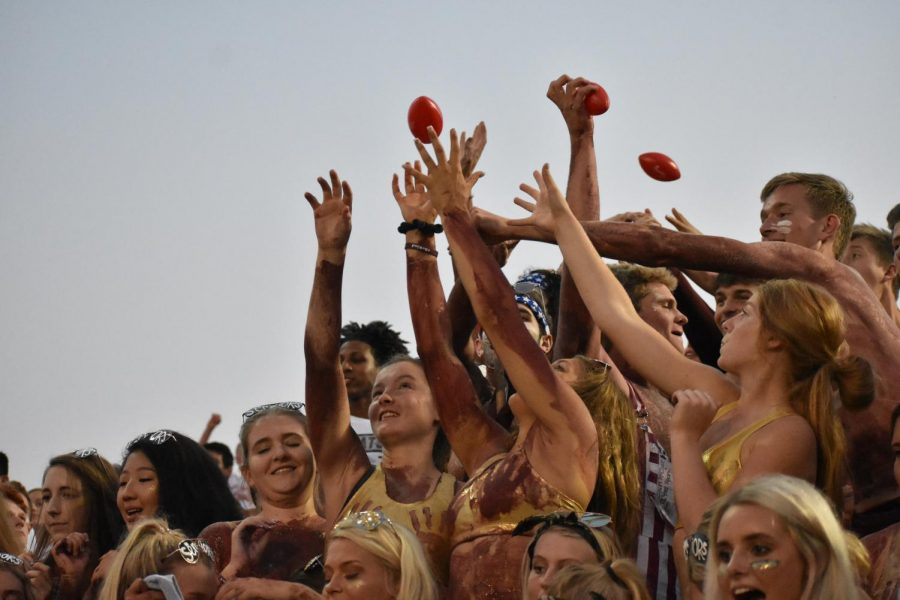 Students compete to catch miniature footballs at the Papio South game