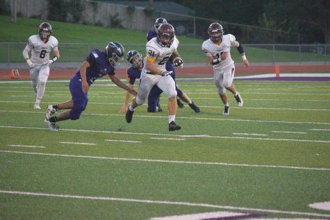 Senior Caden Kirby runs the ball the score a touchdown for the Monarchs.