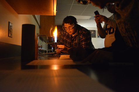 Junior Andrew McMurtry is placing a metal dipped stick into the lab burner during their experiment.