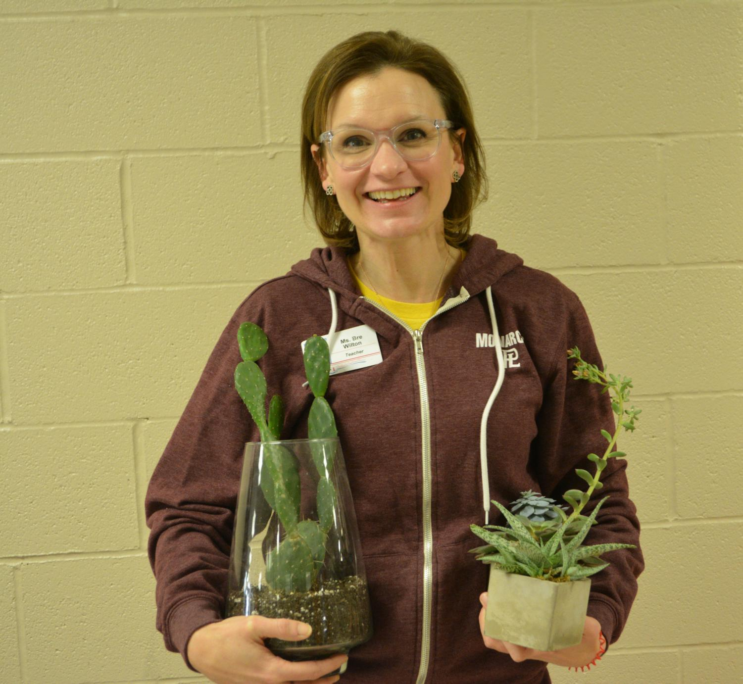History teacher Mrs. Wilton poses with her two favorite plants.