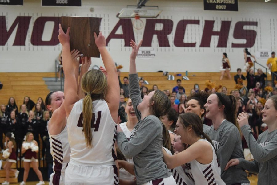 Girls+basketball+huddles+together+after+their+victory+against+Fremont+to+celebrate+their+District+Championship+title.