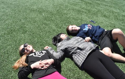 Taryn Moore, Lily Truong and Kyle Struble lounge on the turf after the softball throw competition. When planning the event, the comfort of athletes was a top priority.