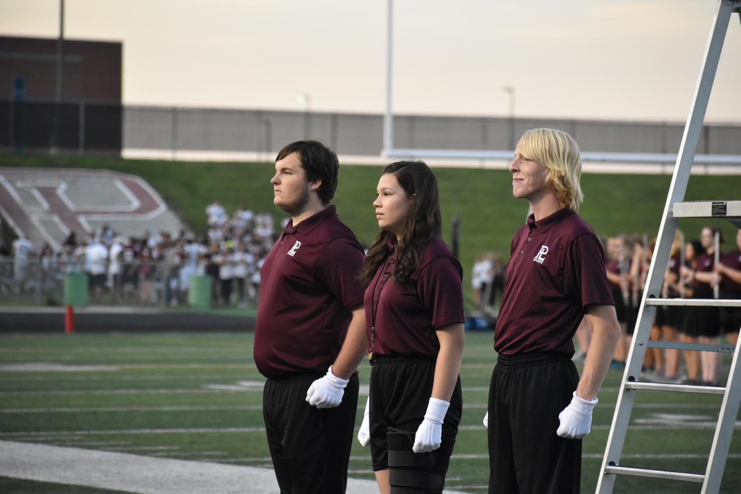 The marching band's three drum majors stand proud before their first full performance. They had a successful halftime, with their entire show on the field.