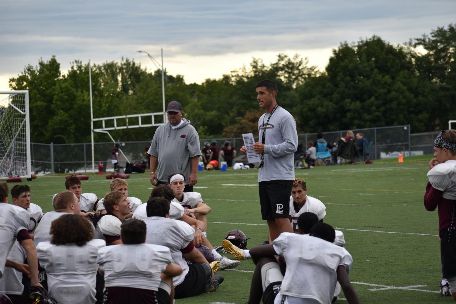 After a morning football  scrimmage at Papillion LaVista High Head Coach Williams addresses the Varsity players on areas of the game that they need to work on.
