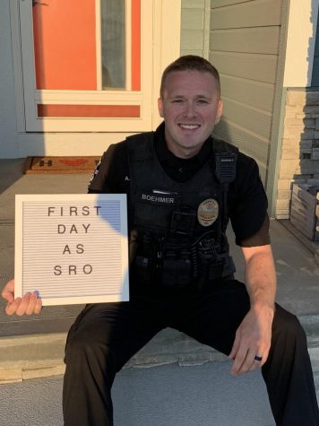 Officer Adam Boehmer poses outside his home before starting his first day as SRO.