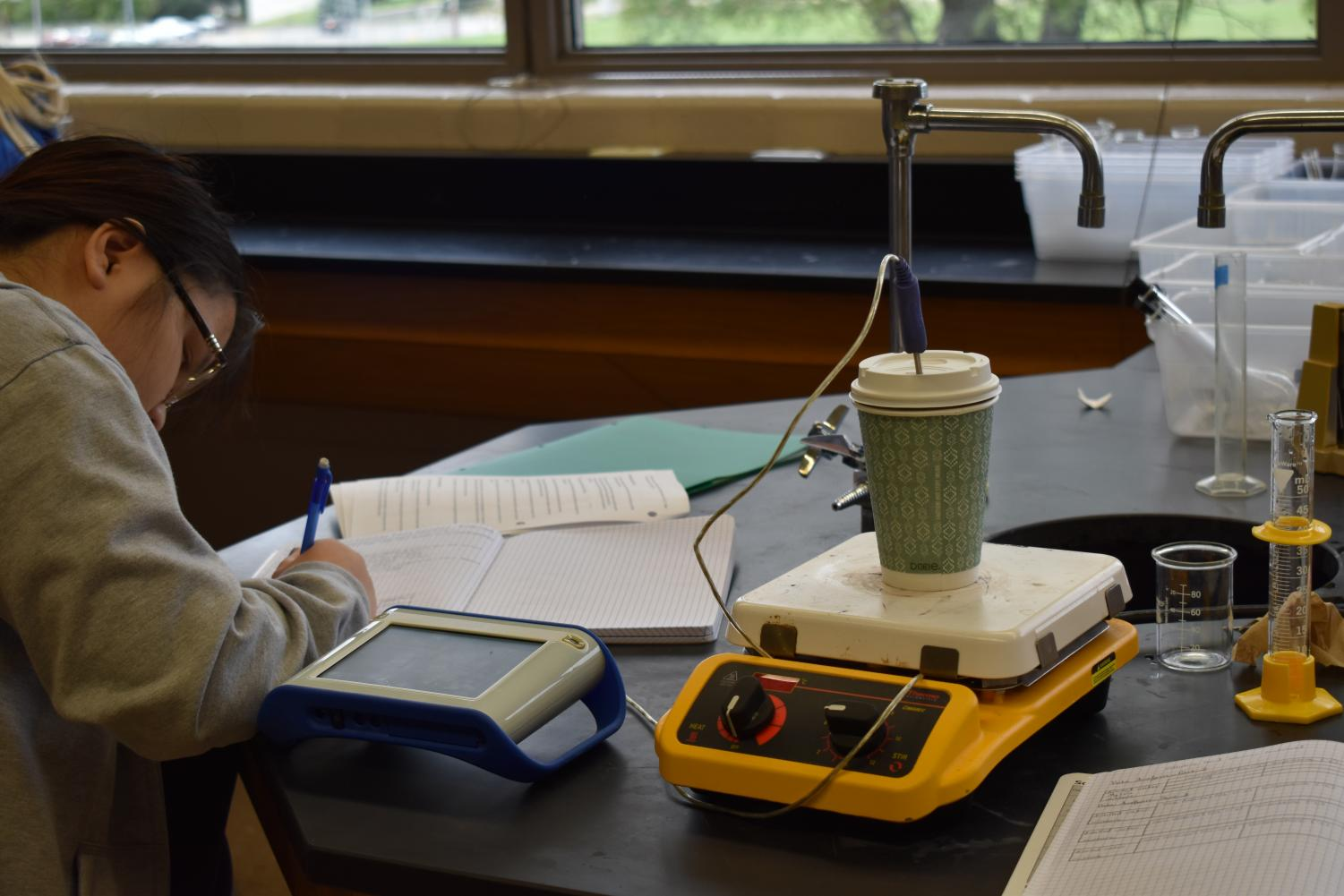 Ann Vu records a the measurements for a lab in AP chemistry