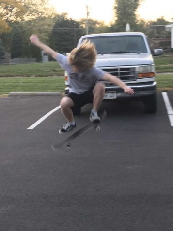 Dayton Conley does an ollie in a parking lot.
