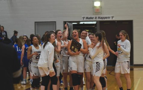 The girls basketball team celebrates their district championship victory.