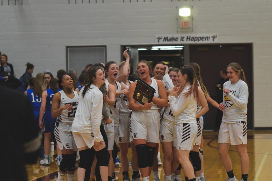 The+girls+basketball+team+celebrates+their+district+championship+victory.