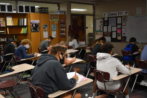 Students take notes during class while taking precautions against Covid-19