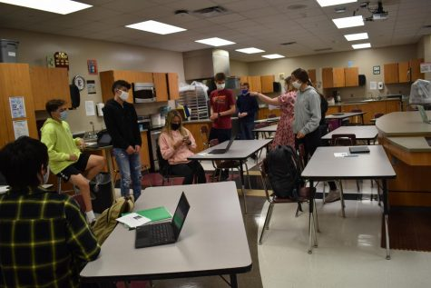 Students in food class stay spread apart while their teacher instructs them.