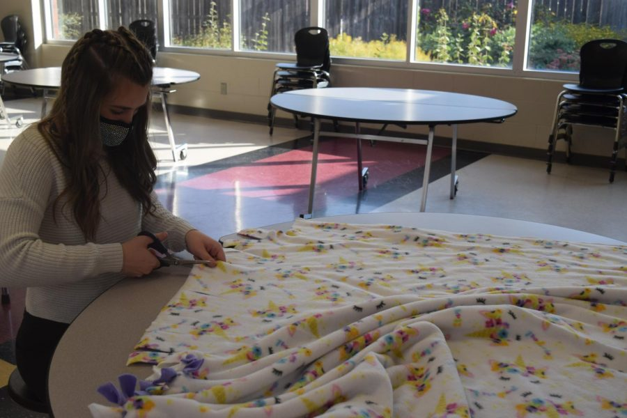Sophomore+Jordan+Bechner+makes+blankets+for+Leo+Club.+The+club+gathered+to+create+blankets+for+the+Linus+Project+this+past+Saturday.+