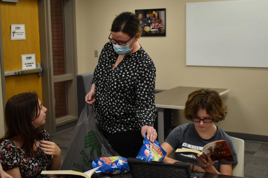 Mrs. Carmen Anderson passes out cotton candy to members of the book club. The book club is reading Full Tilt, which is about a carnival so they are eating carnival themed food.