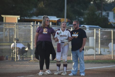 Senior Alex Stoner stands at third base with her parents, laughing at the stories being told on senior night.