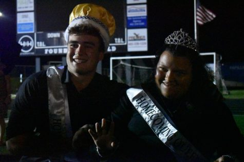 Senior Emma Eberhart honorably strikes a smile towards the crowd as she is crowned homecoming queen, along side homecoming king senior Will Hubert.