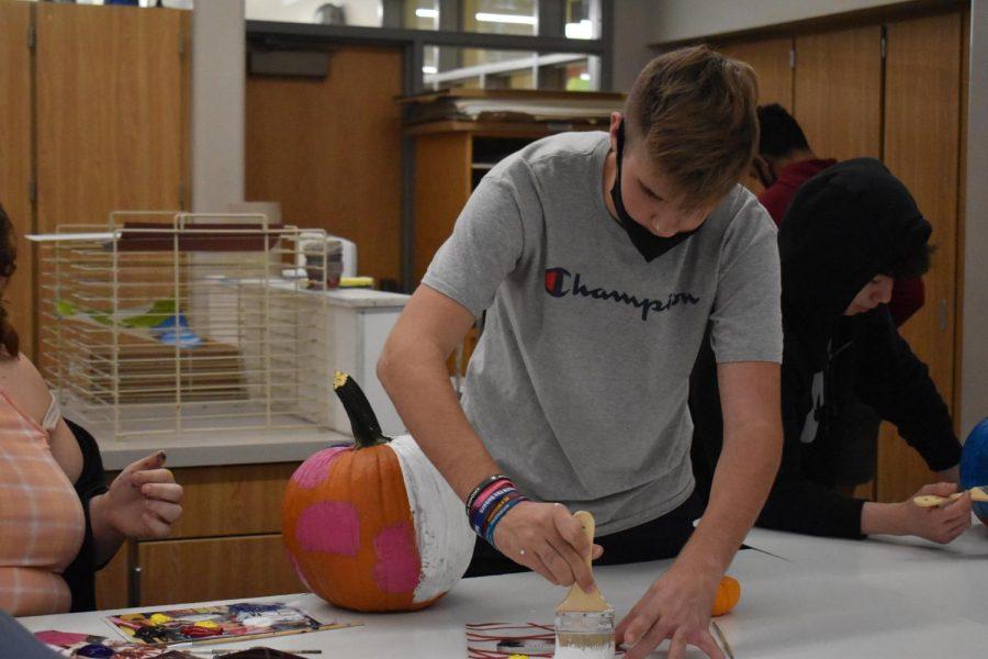 Freshman Max Yeshnowski works with his two friends to make a halloween theme pumpkin.