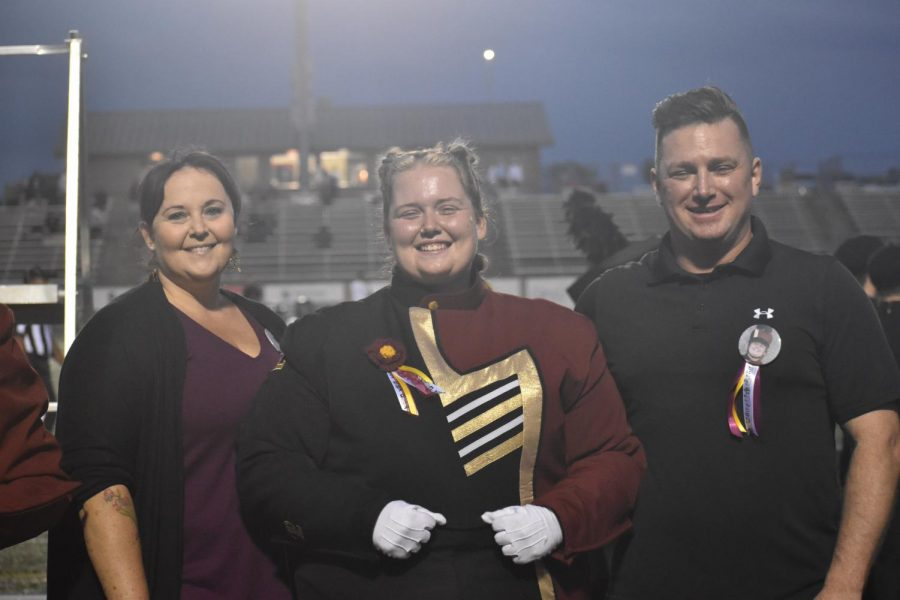 Senior drum major Kiera Miller poses with her parents during her senior night. The band celebrated on September 30.